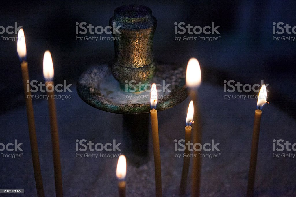 Brass candle holder featuring burning Church candles in Sand stock photo