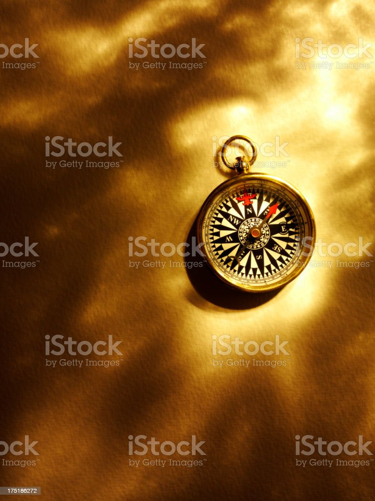 Brass Compass and Gold Lighting on Paper royalty-free stock photo