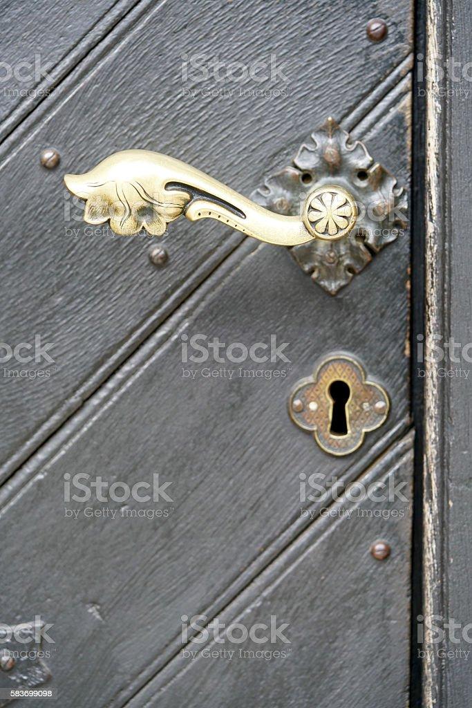 brass door knob of a grey door stock photo