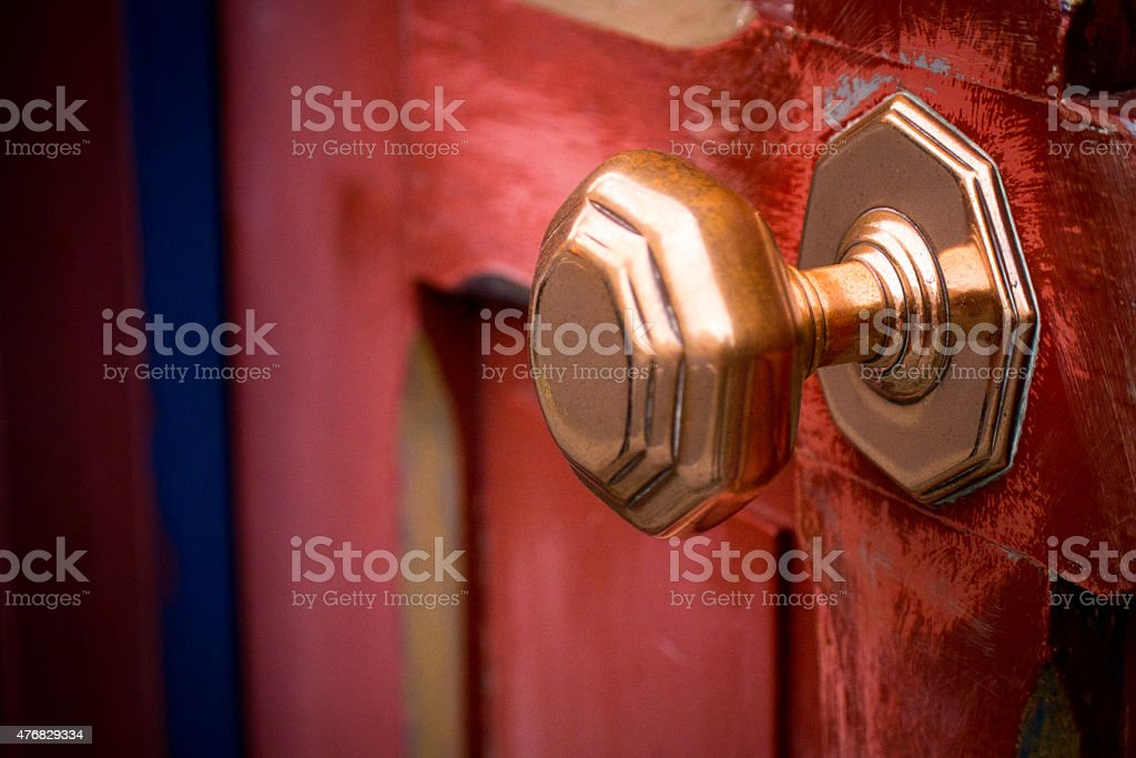 Brass Doorknob on a Weathered Red Door stock photo