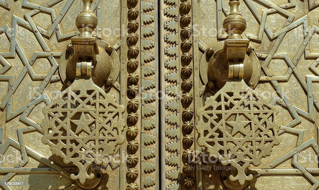 Brass gate with doorknockers royalty-free stock photo