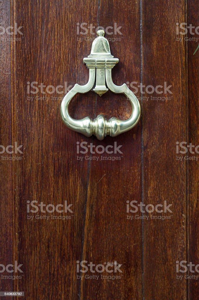 Brass knocker on a door of dark wood stock photo