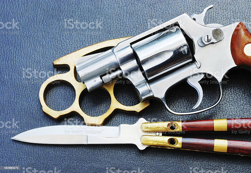 Brass knuckles, revolver and butterfly knife on dark background stock photo