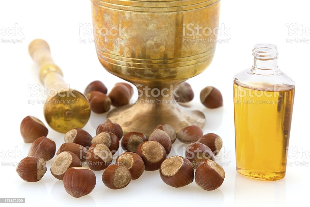 Brass Mortar and Pestle with Hazelnut Oil for cooking stock photo