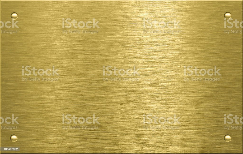 Brass or bronze metal plate with four rivets stock photo