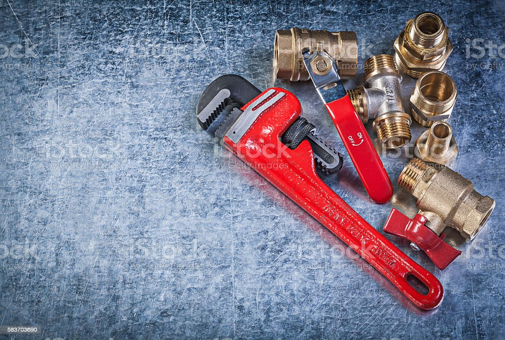 Brass pipe connectors monkey wrench on metallic background plumb stock photo