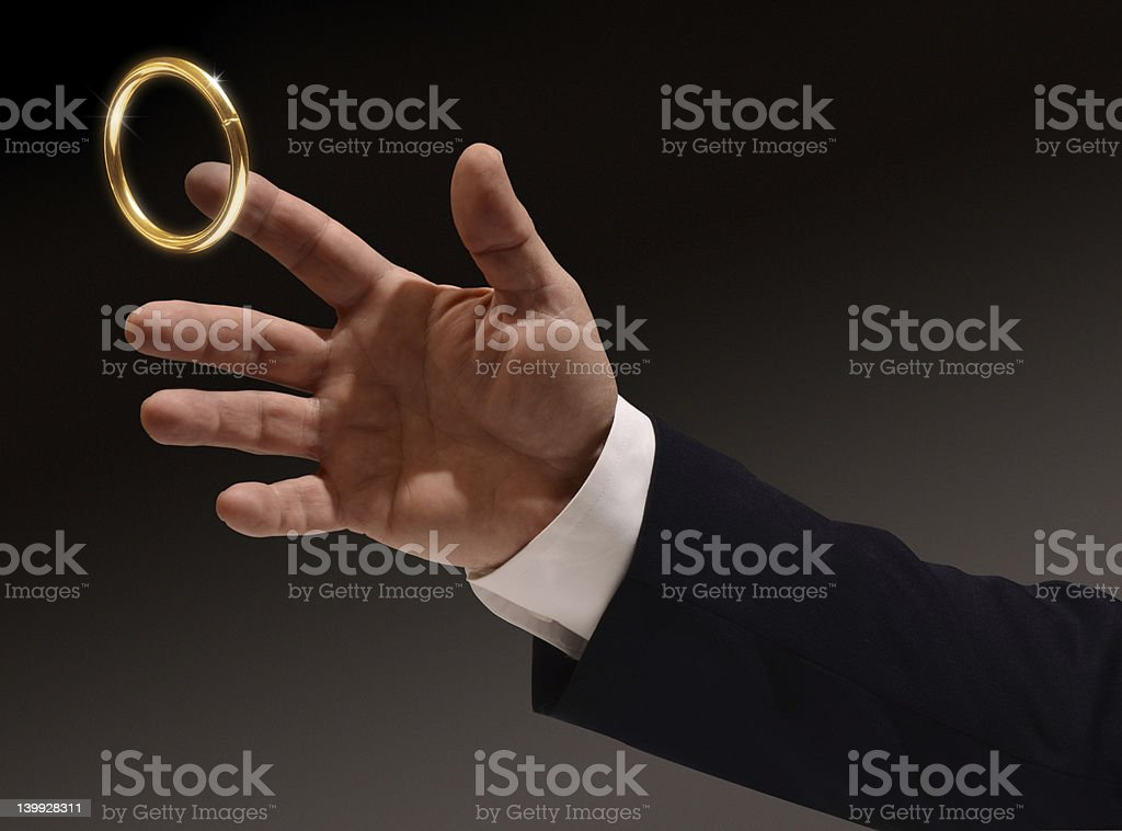 Brass ring being caught by man stock photo