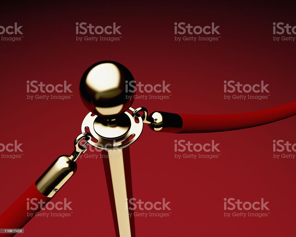 Brass stanchion with red velvet rope stock photo