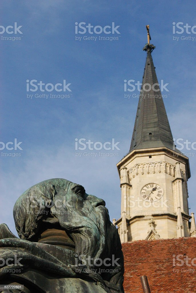 Brass statue and church tower stock photo