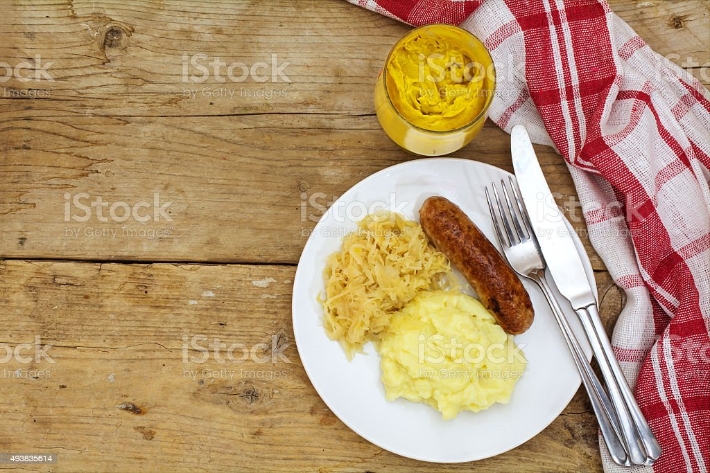 Bratwurst with sauerkraut mashed potatoes and mustard on a rusti stock photo