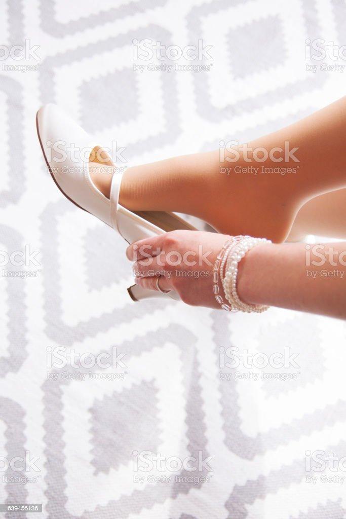 Braut zieht ihre Schuhe an stock photo