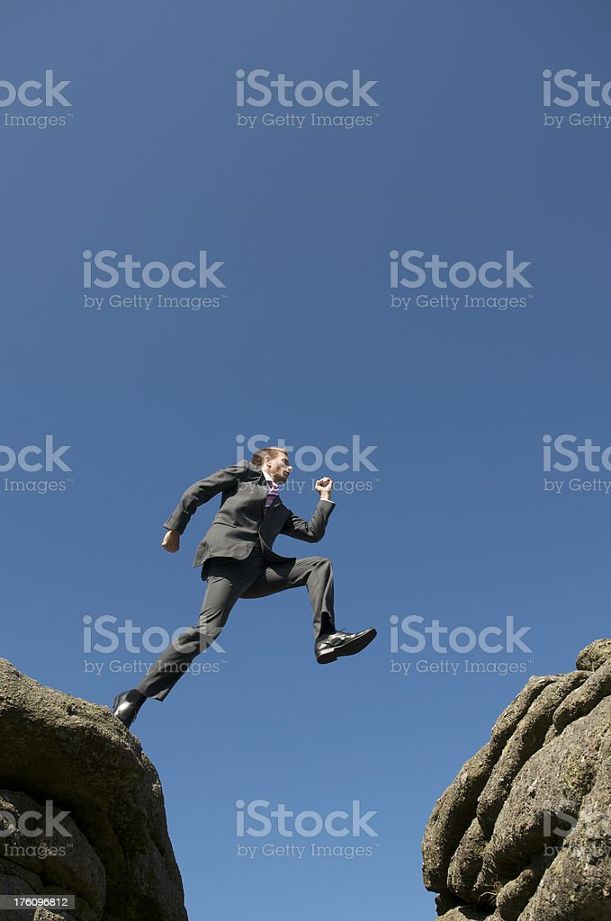 Brave businessman Jumping Outdoors in the Sky Across Rock Crevasse royalty-free stock photo