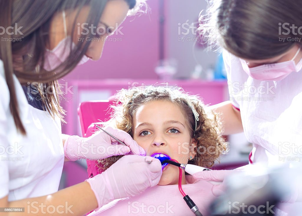 Brave girl sitting in dentist chair and having cavity treatment stock photo