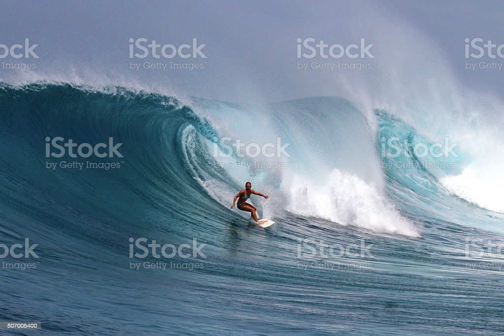 Brave girl surfs a big powerful wave stock photo