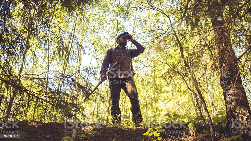 Brave Hiker In Forest Looking Through Binoculars stock photo