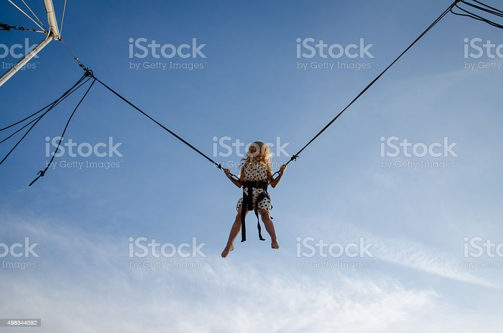 brave kid jumping high up in skies stock photo