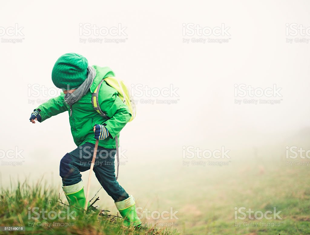 Brave little hiker climbing a hill in mist stock photo