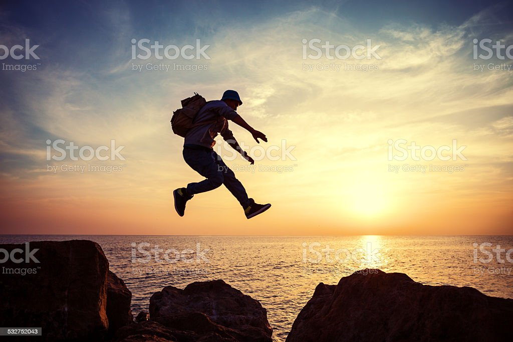 brave man jumping at sunset stock photo