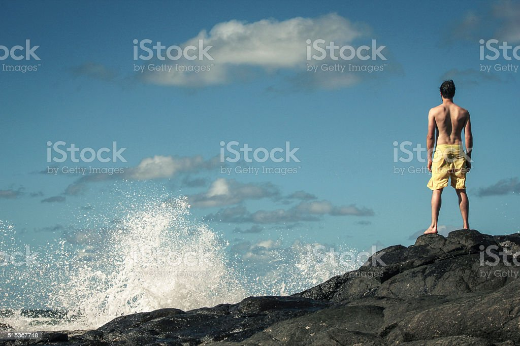 brave man standing on the rocks stock photo