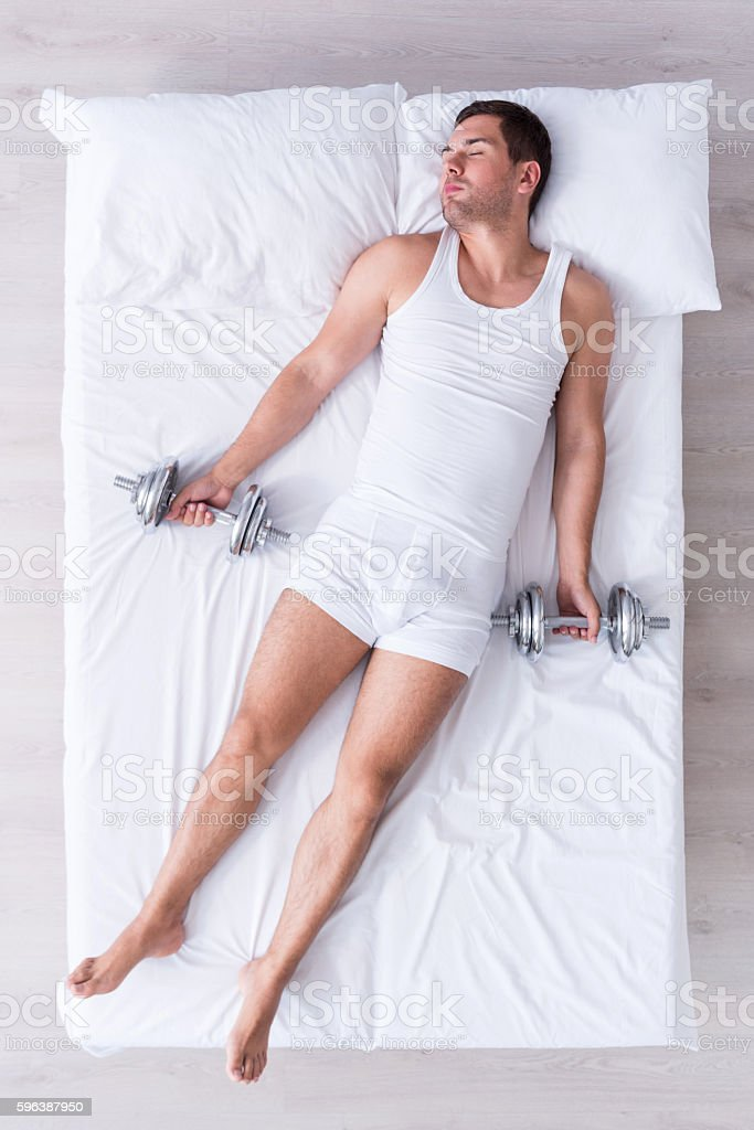 Brave young man sleeping on bed stock photo