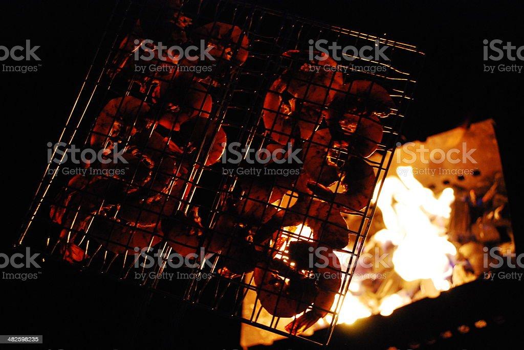 Brazier fire shining through the shrimp in the metal lattice stock photo