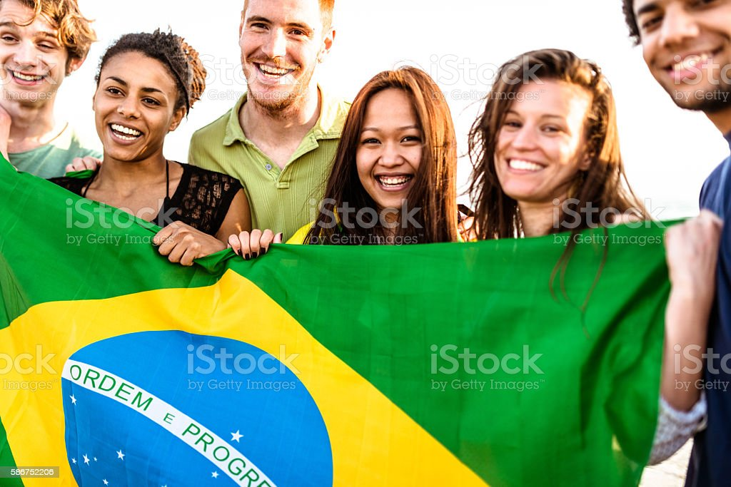 brazil supporter cheering togetherness with brazilian flag stock photo