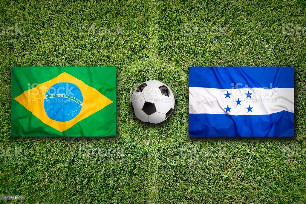 Brazil vs. Honduras flags on soccer field stock photo