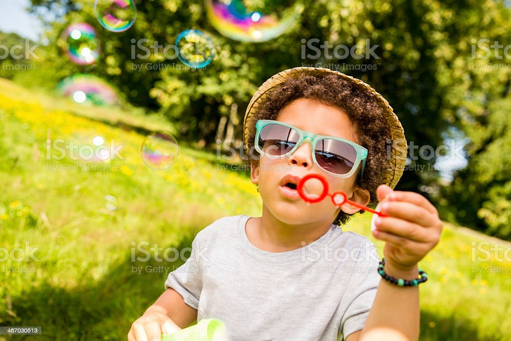 Brazilian boy busy blowing bubbles in nature stock photo