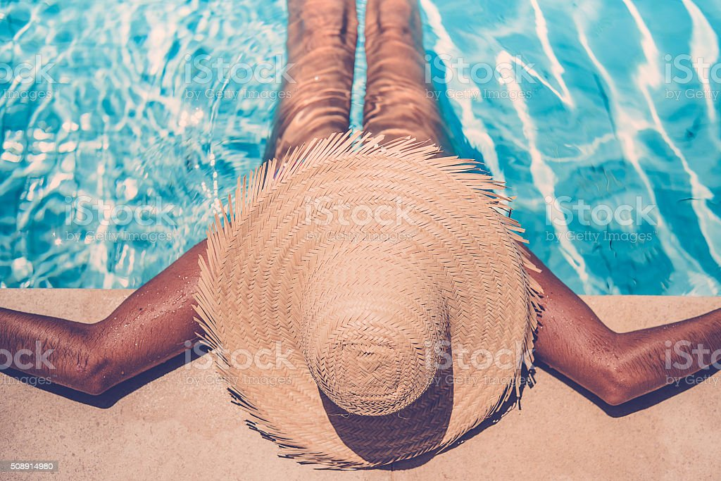 brazilian brown skinned woman with straw hat tanning in pool stock photo