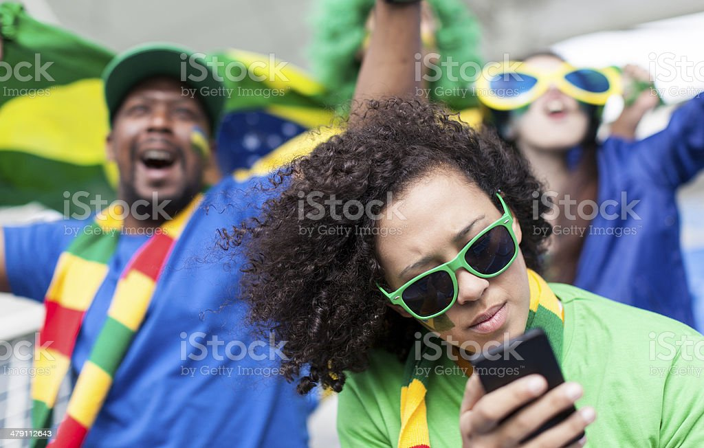 Brazilian fan on her phone while at a soccer match. royalty-free stock photo