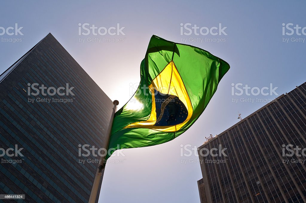 A Brazilian flag in front of skyscrapers stock photo