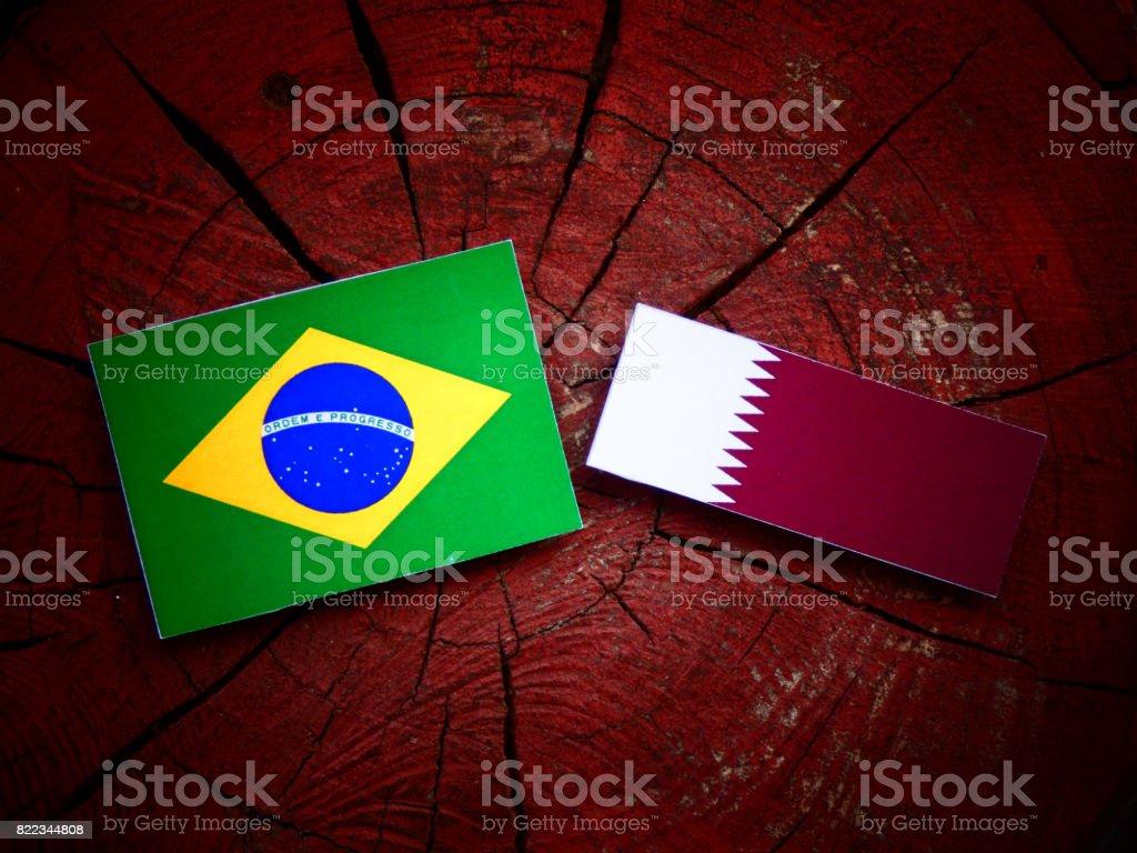 Brazilian flag with Qatari flag on a tree stump isolated stock photo