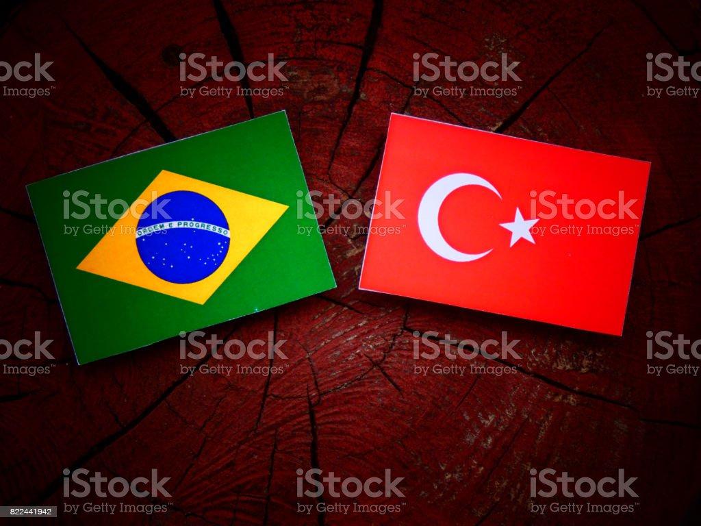 Brazilian flag with Turkish flag on a tree stump isolated stock photo