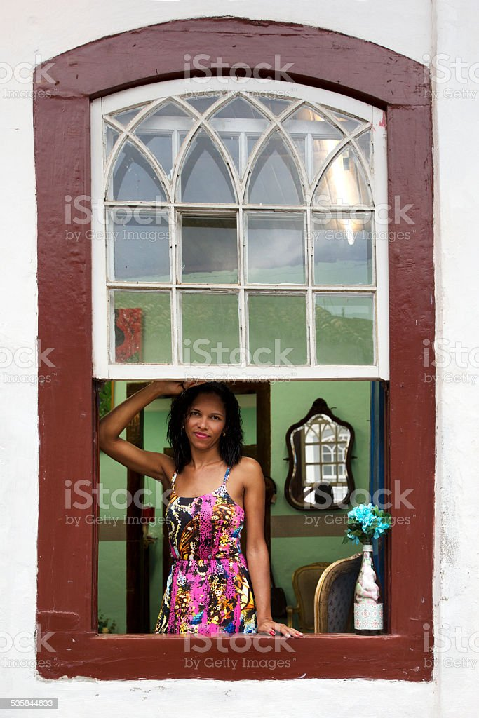 Brazilian girl looking out the window stock photo