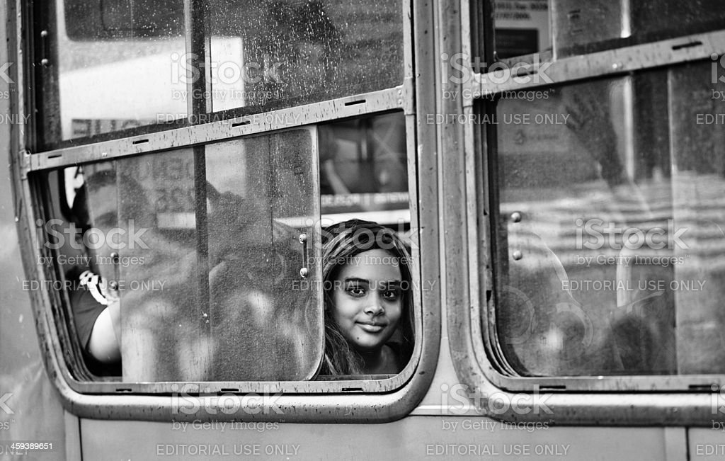 Brazilian girl staring out a rainy window on the bus stock photo