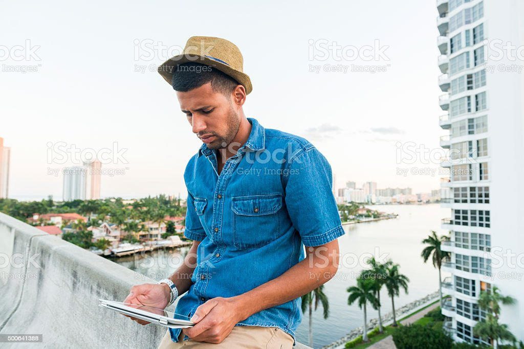 Brazilian Man in 20s Reading Tablet in Tropical Miami Outdoors stock photo