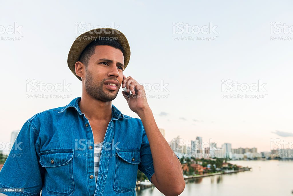 Brazilian Man Listens on Mobile Phone in Tropical Miami Outdoors stock photo