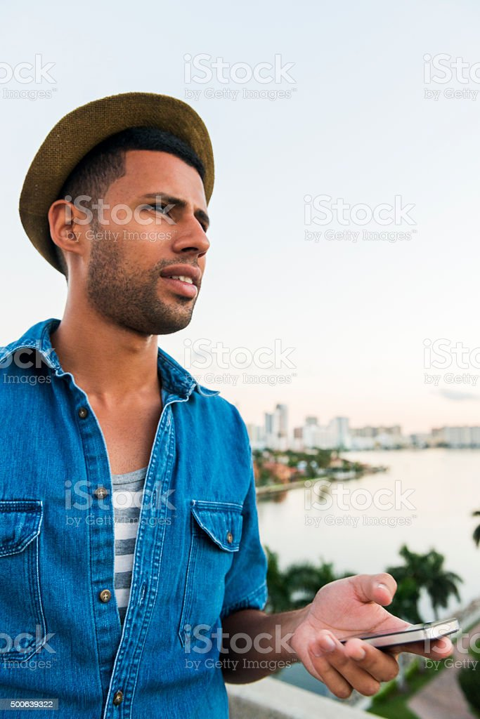 Brazilian Man Looks Up from Mobile Phone in Tropical Miami stock photo
