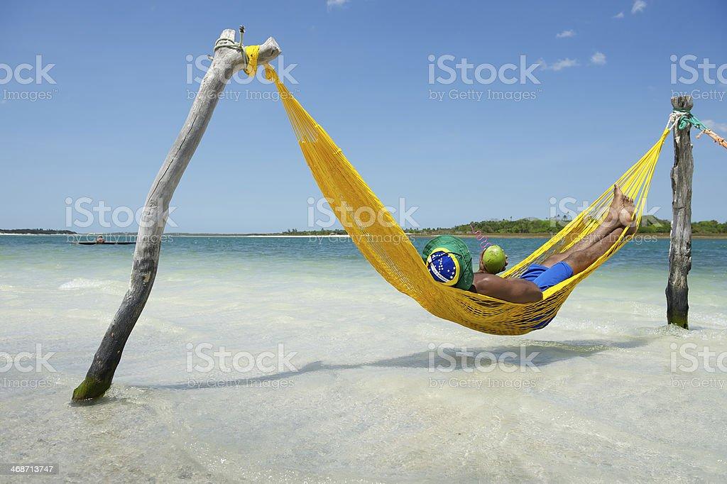 Brazilian Man Relaxing in Beach Hammock with Drinking Coconut stock photo