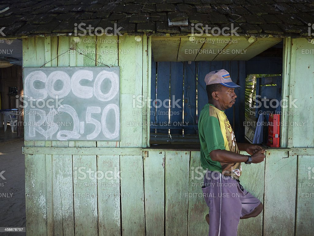Brazilian Man Stands Waiting at Colorful Coco Shack royalty-free stock photo