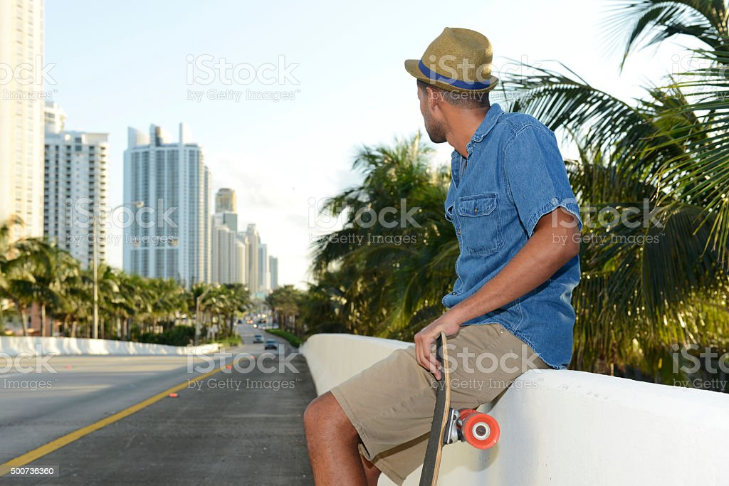 Brazilian Man With Skateboard in Miami Street with Palm Trees stock photo