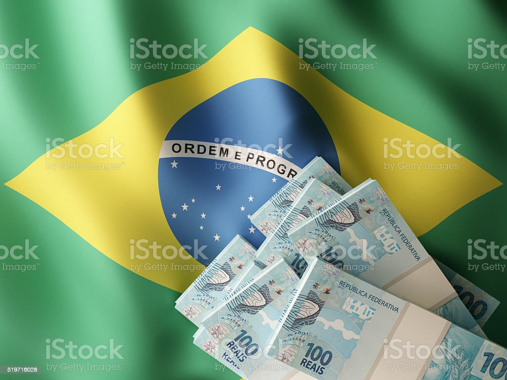 Brazilian real banknotes over Brazil flag stock photo