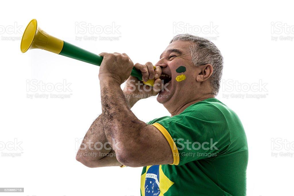 Brazilian senior fan blowing by vuvuzela on white background stock photo
