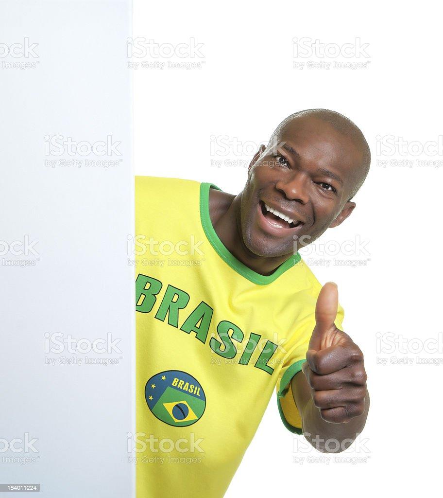 Brazilian soccer fan behind a blank signboard showing thumb royalty-free stock photo