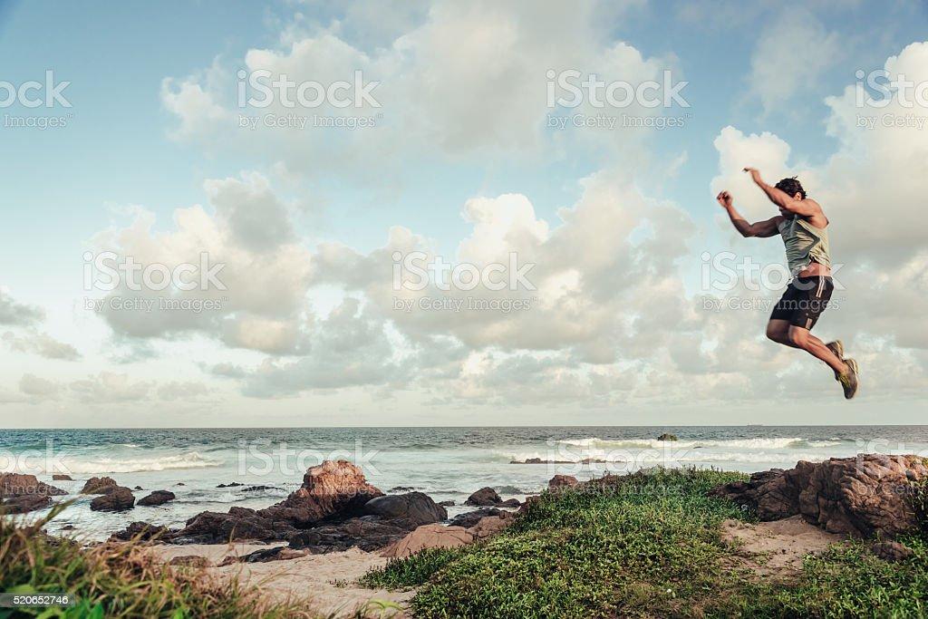 brazilian sportsman jumping high at a beach in evening light stock photo