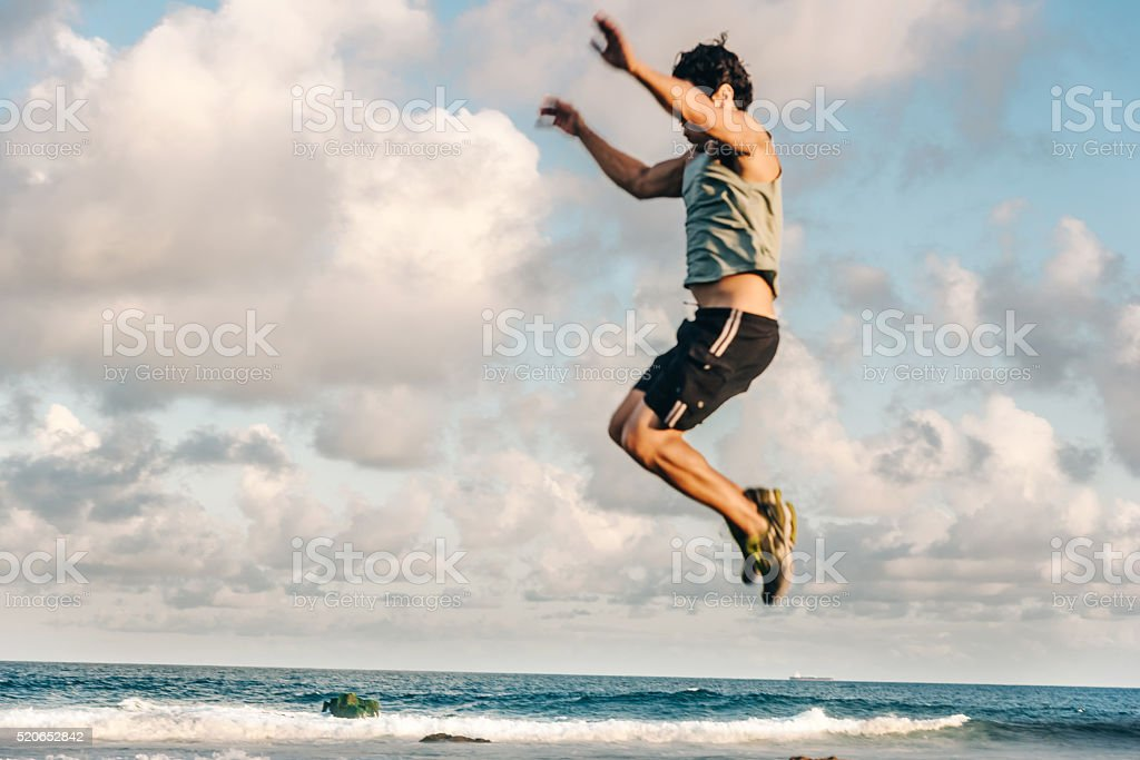 brazilian sportsman jumping high at a coast in evening light stock photo
