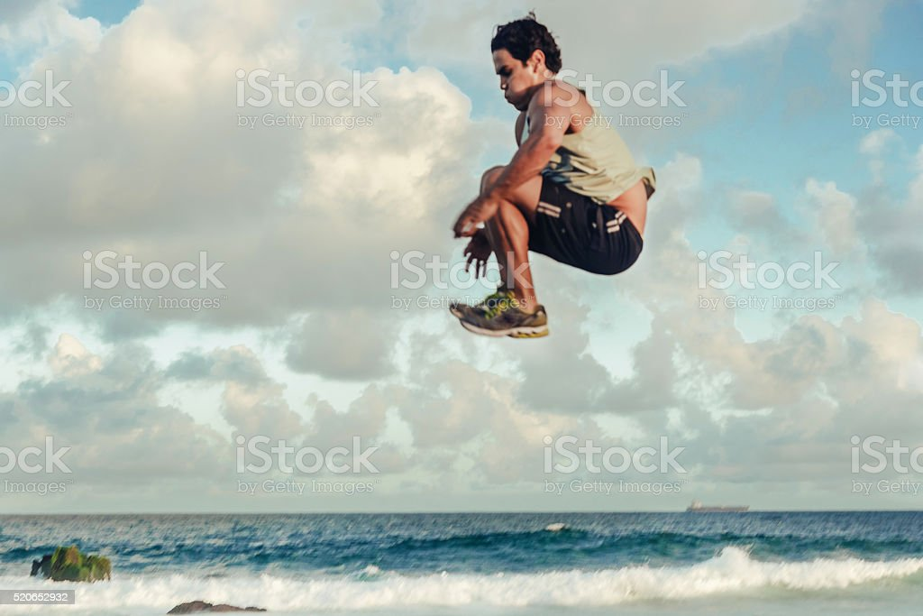 brazilian sportsman jumping high at beach stock photo