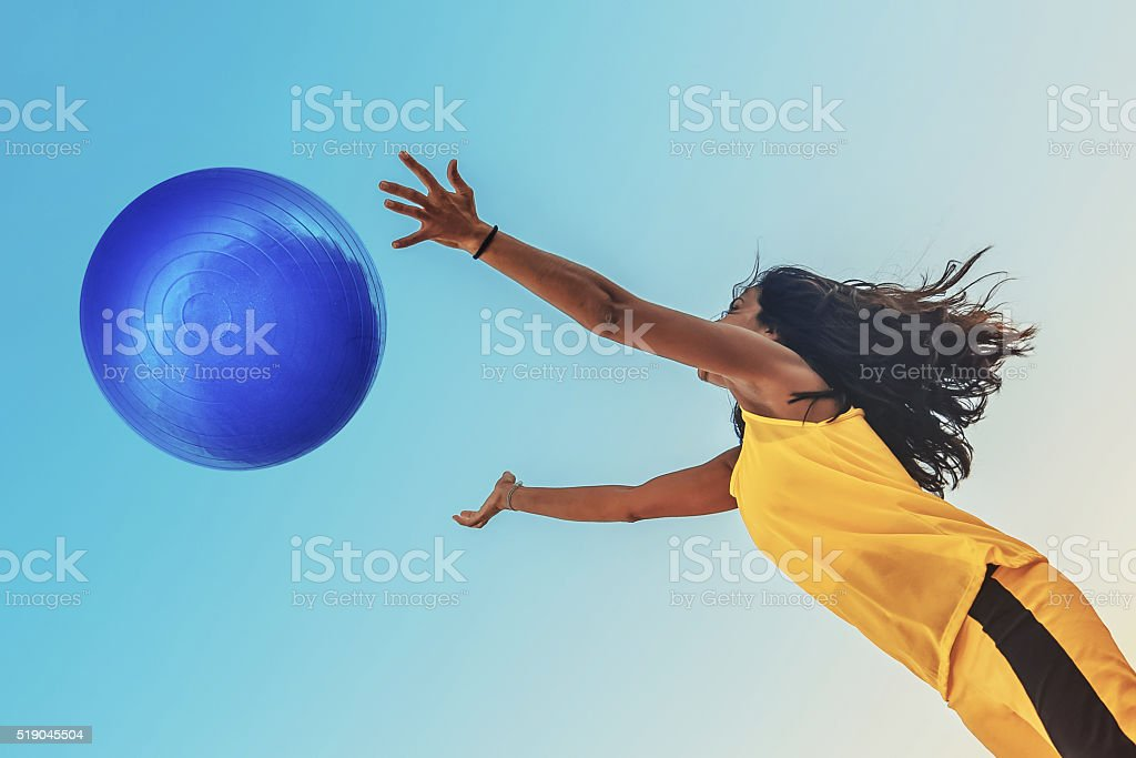 brazilian sportswoman in yellow shirt jumping for blue big ball stock photo