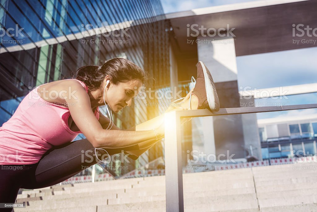 brazilian sportswoman stretching on glass balustrade after running stock photo