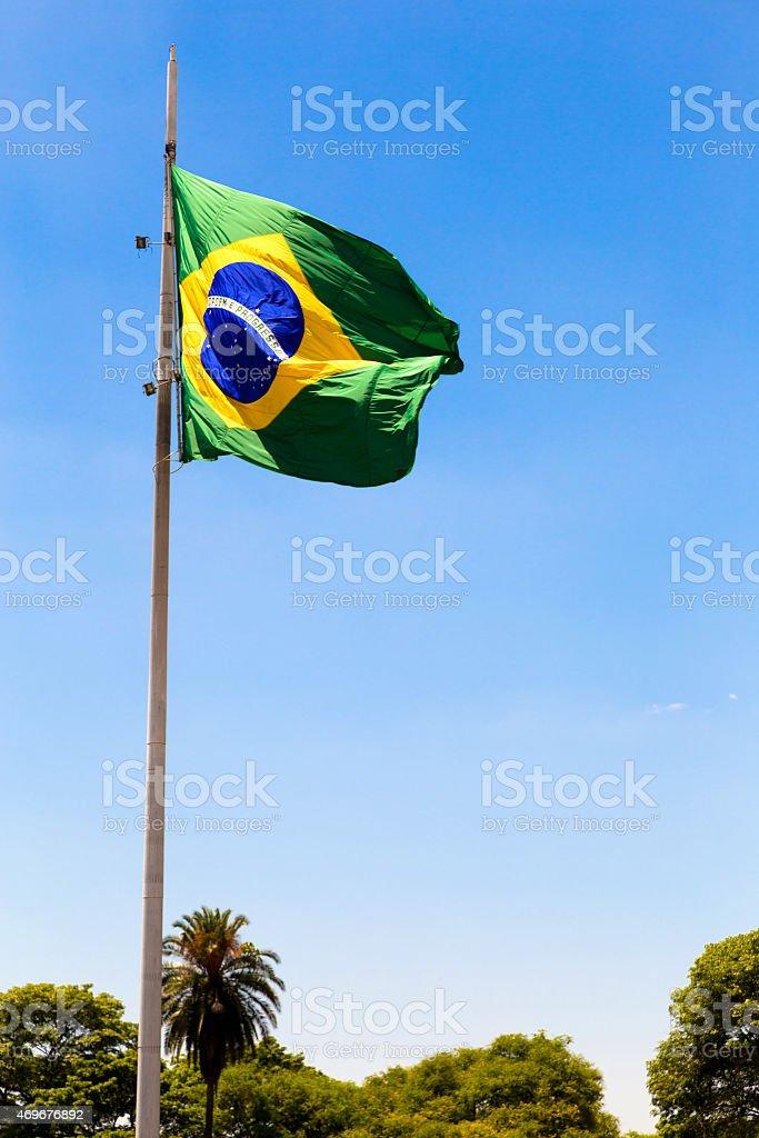 Brazilian waving flag on blue sky stock photo